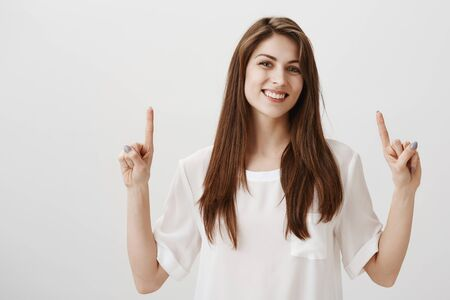Time to be happy. Portrait of good-looking ordinary caucasian woman pointing up with forefingers and smiling cheerfully, showing copy space that is perfect for advertisement, standing over gray wall