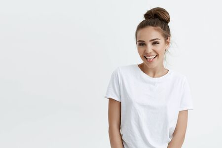 Positive attractive caucasian woman with bun, sticking out tongue and smiling, looking glad and pleased while standing against white background. Charming grown up still has childish attitude to life
