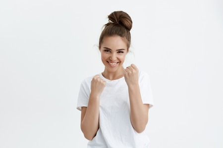 Playful attractive modern woman smiling broadly while raising fists as if she is boxing or defending, punching someone for fun, standing over gray background. Cute girl may seem weak but it is not
