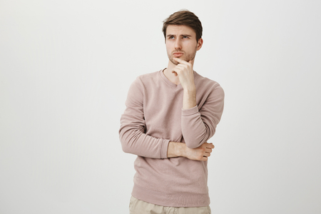 Portrait of attractive young man with bristle looking up while touching chin and thinking about something, standing over gray background in trendy pullover. Maybe I should skip practice today
