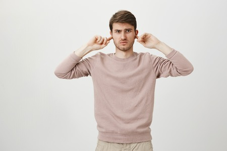 Portrait of confused and annoyed man covering ears with index fingers and looking with dislike at camera while standing over gray background. Guy irritated because of loud alarm on car