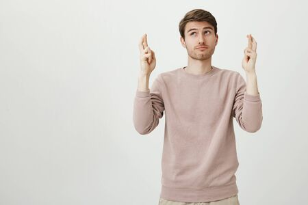 Portrait of dreamy attractive caucasian man looking aside with thoughtful expression while raising hands with crossed fingers, making wish over gray background. Guy begs for end of his shift
