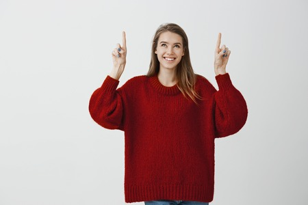 Girl dreams to live in skyscrapper. Dreamy attractive feminine girlfriend in stylish loose sweater, raising index fingers and pointing upwards, smiling broadly, being interested and intrigued Stock Photo