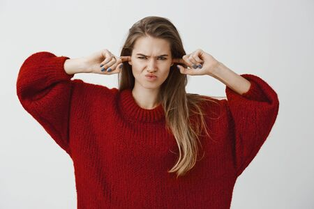 Stop making disturbing noises. Studio shot of displeased annoyed attractive woman in trendy loose sweater, making earplugs with index fingers, covering ears and frowning, hating hear annoying noise