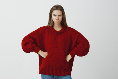 Studio portrait of displased angry caucasian girlfriend in red loose sweater, holding hands on hips and frowning, feeling offended, expressing dislike and disappointment, sulking on boyfriend