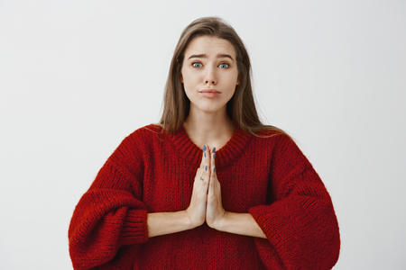 Good-looking caucasian female in red loose sweater, holding hands in pray and lifting eyebrows, begging for apology or asking for help with angel expression and puppy eyes Archivio Fotografico