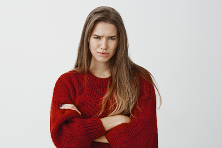 Doubful displeased european female student in red loose sweater, crossing hands and frowning, expressing disbelief and frustration over gray wall