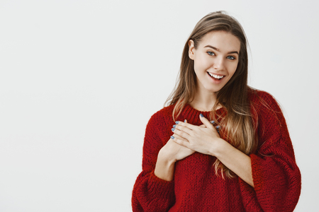 Touched charming european female model in stylish red loose sweater, holding palm on chest and smiling from satisfaction over gray wall