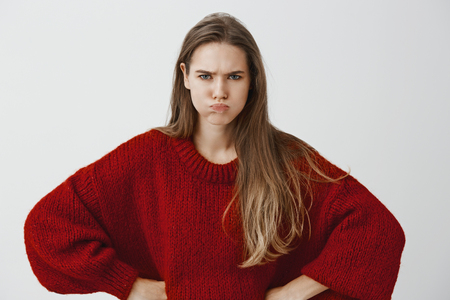 Portrait of displeased offended european woman in red loose sweater, holding hands on hips, sulking and frowning, arguing and being insulted over gray background Stock Photo