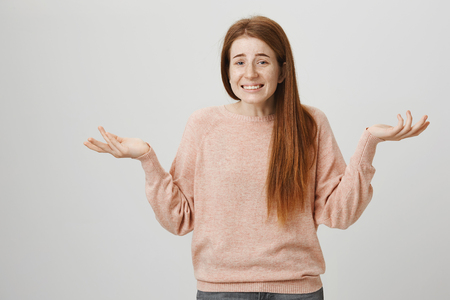 Indoor shot of attractive redhead girl with freckles shrugging with raised hands, smiling cluelessly or saying oops, standing over gray background.