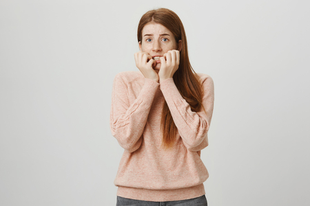 Portrait of beautiful redhead european woman expressing fright, being scared and holding hands near mouth, staring aside and wanting escape, standing against gray background.