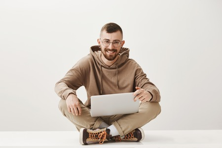Studio portrait of handsome happy caucasian male with fair hair and beard, wearing glasses sitting on floor with notebook on laps, being ready to work hard, enthusiastic over gray wall