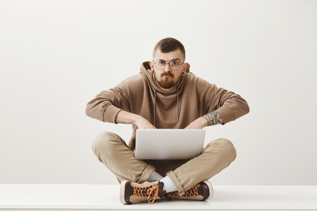 Annoyed outraged cute bearded man, sitting on floor with laptop on laps, typing staring with scary bothered expression at camera, frowning over gray wall Stock Photo