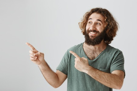 Portrait of happy optimistic eastern male with curly hair and beard looking and pointing left with both index fingers, smiling and expressing interest and satisfaction Archivio Fotografico