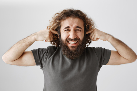 Sick and tired adult male with curly hair and beard shutting ears with index fingers, grimacing from displeased emotions, being annoyed with sound or quarrels Stock Photo
