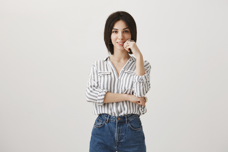 Attractive woman with short dark hair in stylish striped blouse standing in partial arm-cross pose, holding finger on lip as she intrigued or curious Stock Photo