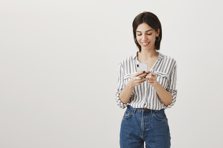 Portrait of successful happy adult woman in fashionable clothes holding smartphone looking at screen while typing over gray wall