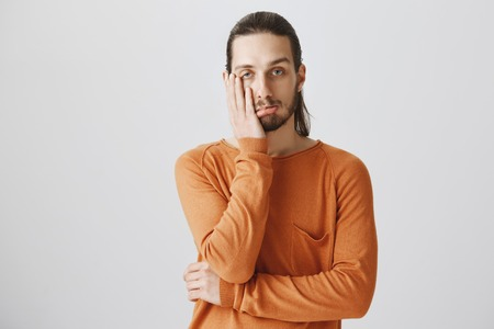 Portrait of tired and bored attractive guy in casual orange pullover, holding palm on cheek and pouting, being indifferent and uninterested in discussion over gray wall