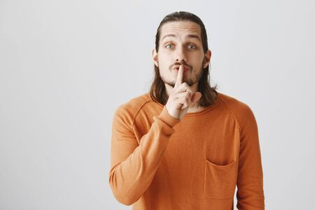 Portrait of handsome friendly-looking man in orange sweater bending towards camera, saying shh while holding index finger over mouth, showing shush gesture to ask keep voice down