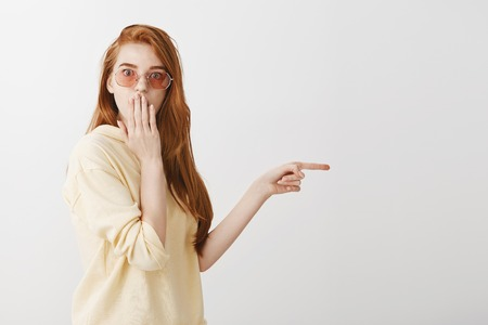 Woman is speechless after witnessing something shocking. Beautiful young european redhead standing half-turned in stylish clothes and glasses pointing right, covering mouth while gasping from surprise