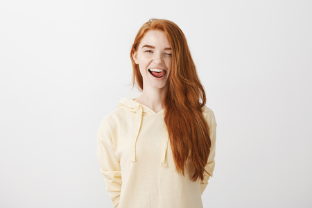 Portrait of good-looking positive redhead girl in trendy yellow hoodie showing tongue and winking, being in playful mood while seducing attractive guy