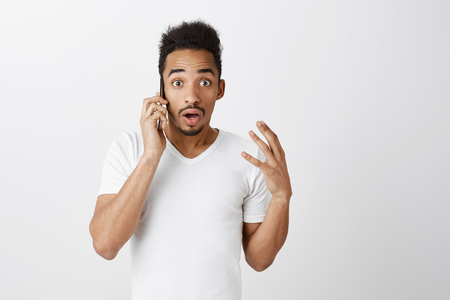 Indoor shot of nervous shocked attractive guy with afro haircut shaking hand while talking on smartphone, dropping jaw from surprise and wonder, standing over gray wall Stock Photo