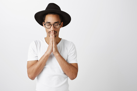 Portrait of focused serious african-american in stylish eyewear and black hat, holding hands in pray over mouth, closing eyes while praying or making wish