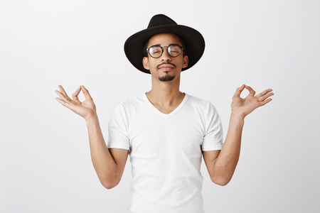 Studio portrait of relaxed handsome african-american fashion designer in stylish glasses and hat, raising hands with zen gesture, meditating or doing yoga, calming down