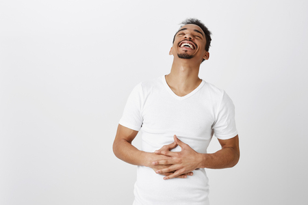 Portrait of carefree attractive male student in white t-shirt, hearing funny joke, laughing out loud, feeling pain in belly muscles from chuckle, standing over gray wall