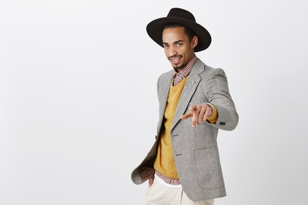 Confident fashionable dark-skinned male model in trendy black hat and gray jacket pointing at camera, being self-assured over gray wall Stock Photo