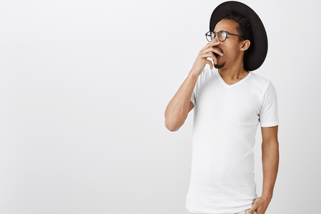 Studio shot of handsome stylish african-american in trendy glasses and black hat, turning away from camera, yawning from exhaustment, being sleepy over gray background