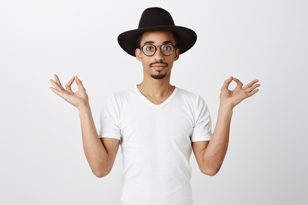 Portrait of stylish attractive dark-skinned hipster in black hat and trendy fake glasses spread hands with zen gesture, meditating or interesting in yoga