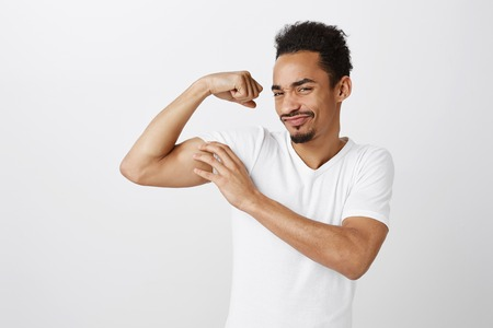 Portrait of satisfied arrogant young man with curly hair, raising arm, touching muscle, bragging about good body condition, working out in gym, standing over gray wall