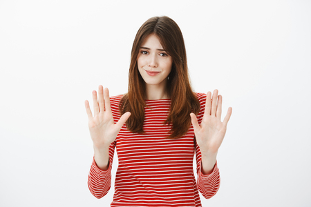 Portrait of uncomfortable pretty brunette, raising palms in no or stop gesture, smiling awkwardly, wanting to decline offer politely, feeling insecure and nervous Stock Photo