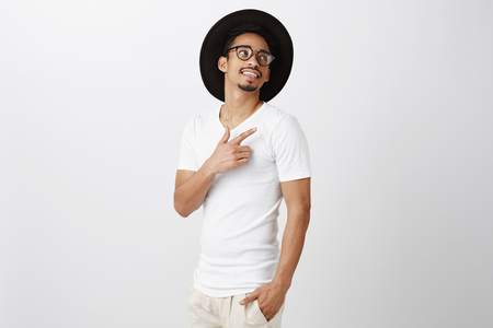 Stylish urban african-american in black hat and glasses standing half-turned over gray background, pointing and looking at upper right corner, intrigued and curious Stock Photo