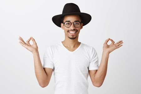 Studio portrait of good-looking african man in trendy eyewear and black hat, raising hands with zen gesture, smiling broadly, suggesting start meditating or doing yoga Stock Photo