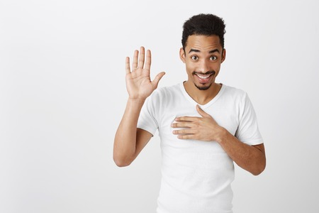 Studio shot of sincere happy african-american male with afro haircut, raising palm and holding hand on chest, promising to me honest, standing over gray background