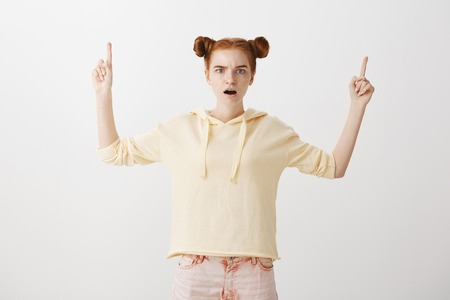 Portrait of attractive slender redhead female student dropping jaw from shock and amazement, pointing upwards with raised index fingers, surprised over gray wall