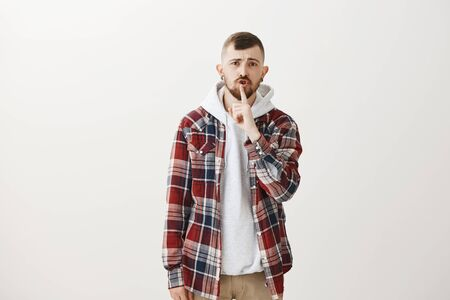 Serious charming european male model with beard and trendy haircut, saying shush whule making shh gesture with index finger over mouth, wanting silence or keep voice down Stock Photo
