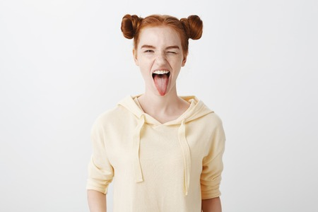Indoor shot of attractive caucasian ginger girl with two buns hairstyle sticking out tongue and winking at camera, being in playful mood, ready to rock n roll