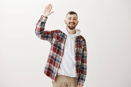 Carefree friendly male student in stylish clothes, raising palm to give high five, greeting best friend or waving, smiling broadly, hanging out with mates in city centre, standing over gray wall