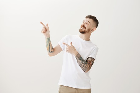 Good-looking funny european male model with beard and tattoos, pointing and looking at upper left corner, smiling broadly, being in great mood while hanging out in club with friends after work