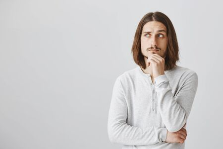 Studio shot of handsome smart guy with long fair hair holding hand on chin and looking up, thinking or making idea in mind, creating plan of new concept, standing against gray background Stock Photo