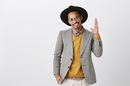 Shot of confident handsome dark-skinned businessman in luxury clothes, hat and trendy glasses raising palm to direct at himself, nominating over gray wall