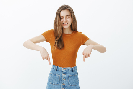 Portrait of satisfied happy fair-haired european female model in stylish outfit, looking and pointing down with index figers, smiling, laughing from joy and positive emotions, showing joyful attitude 写真素材
