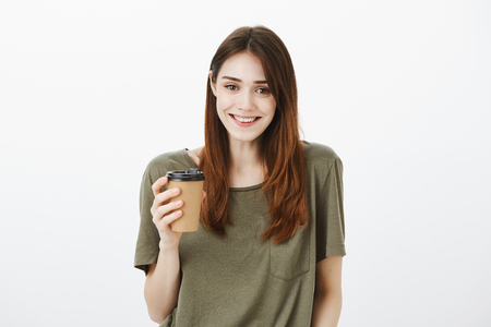 Happy positive woman with bright smile, holding coffee, drinking beverage and liking conversation, feeling relaxed and joyful