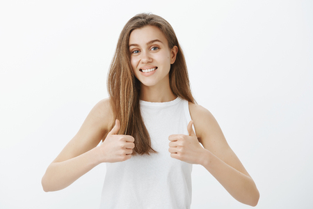 Portrait of good-looking friendly and outgoing girl with blond hair, showing thumbs up and smiling broadly, liking idea or concept and giving permission to continue over gray wall