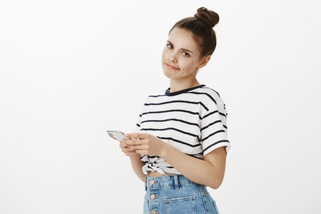 Girl feeling regret after missing interesting lecture. Portrait of upset good-looking female with bun hairstyle, standing half-turned with smartphone, showing disappointment over white background