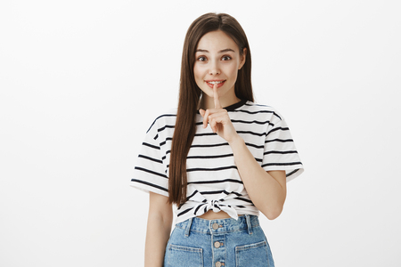 Girl makes surprise party for boyfriend, asking to keep it secret. Cute kind good-looking caucasian female in striped t-shirt, showing shh or shush sign with index finger over mouth, smiling tenderly
