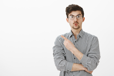 Wow, amazing. Surprised interested european man with beard and moustache in glasses, folding lips and pointing at upper left corner, being intrigued and curious, asking assistant to show closer item Stock Photo